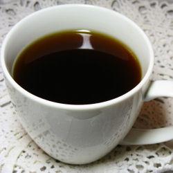 Mustaa keitettyä kahvia valkoisessa kupissa. Taustalla pitsiliinaa.
