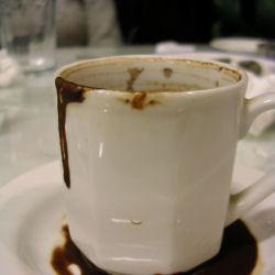 Mustaa kahvia, jota valuu valkoisen kupin alla olevalle kahvilautaselle.