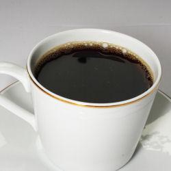 Mustaa kahvia valkoisessa kahvikupissa. Kupin alla valkoinen lautanen.